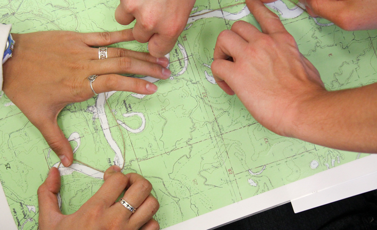 students tracing path on map with their hands