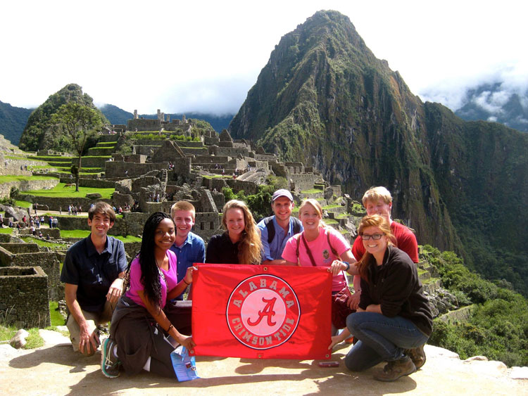 a group of UA students holding a UA banner with ruins in the background